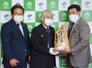 大津理事長(中央)から寄付を受け取る元山村長(右) =6日、宇検村役場