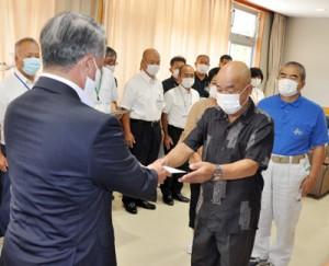 伊集院村長(左)から助成金を受け取る村区長会の中井会長=2日、大和村防災センター