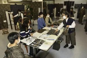 龍郷柄展で柄の成り立ちについて発表した内山さん(右)=29日、奄美市名瀬