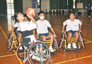1対3のゲームなどを通し、中学生らに車いすバスケのルールや楽しさを伝えた網本さん(左)=13日、大和村立大和中体育館
