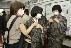 講師の手ほどきを受けながら着付けを学ぶ生徒ら=13日、奄美市名瀬の崎原小中学校