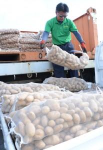 バレイショの種芋を軽貨物車に積み込む作業員=10月28日、和泊町