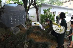 文学碑に献花する島尾伸三さん(左)ら=12日、奄美市名瀬