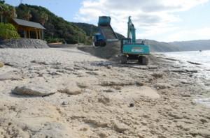 露岩が目立つ海岸に次々と砂を投入するトラック=26日、奄美市名瀬