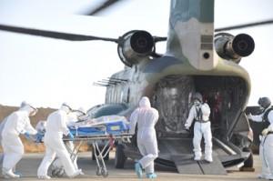空自の輸送ヘリに患者を運ぶ訓練参加者=2日、徳之島町の亀津新漁港