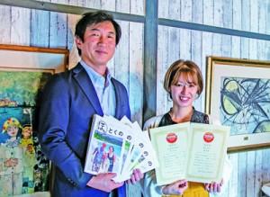 日本地域情報コンテンツ大賞の観光部門で優秀賞を受賞したフリーペーパー「ほっとくの」を手にするモスク・クリエイションの近藤代表取締役(左)=提供写真