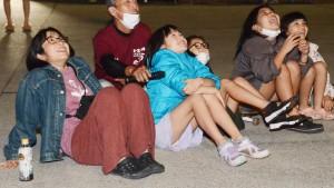 舞い上がった夜空の花火に歓声を上げる市集落の子どもたち=21日、奄美市住用町