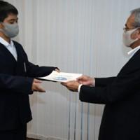 朝山会長から賞状を受け取る重田君(左)=25日、奄美市役所