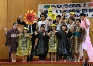 島口劇を披露し、保護者ら観客に手を振る児童生徒ら=1日、奄美市住用町の市小中学校