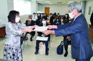 加納委員長(右)から当選証書を受け取った新議員ら=23日、瀬戸内町役場