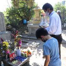 墓前に線香をあげ、先祖に感謝する参拝者=15日、喜界町湾