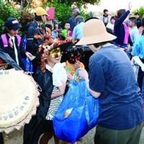 踊りを終え餅やお菓子を受け取る仮装した子どもたち=10月31日、伊仙町阿権