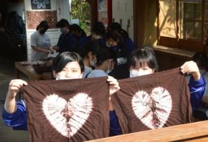見事な染め上がりに笑顔を見せる奄美高校の生徒=11日、龍郷町の大島紬村