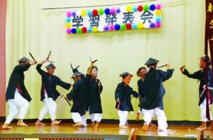 ユーモラスな面を付け大人顔負けのリズム感と手踊りで「諸鈍シバヤ」を披露した男子児童生徒=1日、諸鈍小中学校