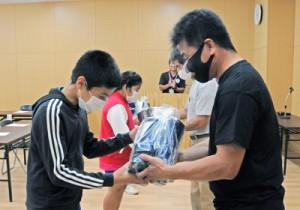 開始式で、受け入れ農家から体験で使う雨靴と手袋をプレゼントされた子どもたち=12日、和泊町