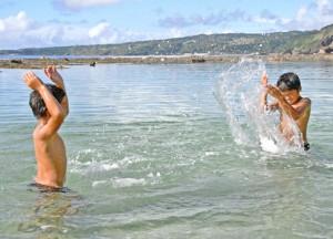 海辺で水遊びを楽しむ子ども=7日、伊仙町瀬田海海浜公園