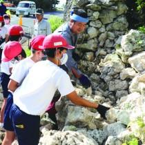 保存会の指導で石垣を修復する早町小の児童ら=14日、喜界町の阿伝集落