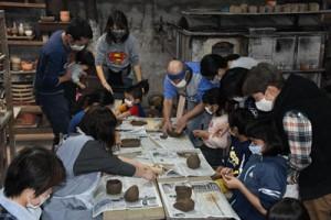 親子連れ約20人が陶芸に挑戦した奄美手熟師会子ども講習会=29日、奄美市名瀬の陶器工房「野茶坊焼」