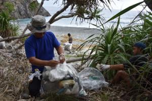 漂着ごみを回収するダイビング事業者=25日、瀬戸内町蘇刈のホノホシ海岸