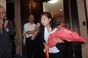 花束を手に、目を潤ませながら支持者にあいさつする永井さん=22日午後10時ごろ、瀬戸内町古仁屋