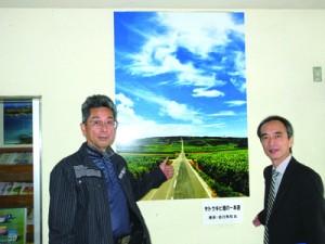 「サトウキビ畑の一本道」パネル展示が始まった支庁喜界事務所。左は撮影した吉行さん=14日、喜界町赤連