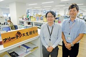 フリーランス支援窓口を掲げる奄美市商工情報課の(右から)中江康仁係長、森永健介さん
