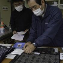 反物の出来上がりを見る検査担当者=28日、奄美市名瀬の紬協組