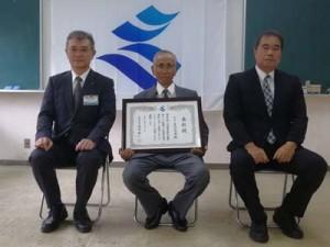 道路愛護知事表彰を受けたウロー美化同志会の田中代表(中央)ら=3日、与論町