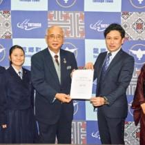 竹田町長(中央)に提言書を提出したたつごうみらい会議の福本座長ら=4日、龍郷町役場