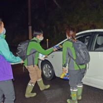 ドライバーにアマミノクロウサギの交通事故防止を呼び掛けた環境省の職員=24日、瀬戸内町