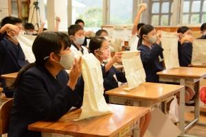 東京都の泰明小から届いた柳染めのハンカチを掲げてお礼を伝える大勝小の児童たち=4日、龍郷町