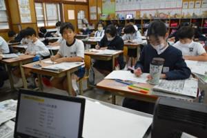 熱心にメモを取りながら新聞社の働きについて学ぶ児童=17日、瀬戸内町の古仁屋小学校