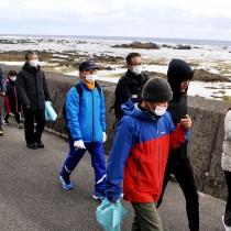 海岸沿いのサイクリングロードを歩く奄美トレイル開通記念ウオークの参加者=20日、奄美市笠利町