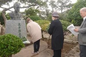 67年前に日本復帰を果たした先人たちをしのび、泉芳朗の胸像に献花する市民=25日、奄美市名瀬のおがみ山公園