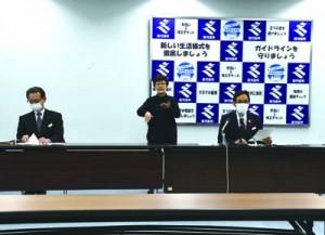 徳之島町でのクラスター発生を発表する県の地頭所恵くらし保健福祉部長(右)=7日、鹿児島市の県庁