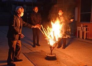 復帰運動時を再現したかがり火の前で当時の様子などを語り合う参加者=25日、奄美市名瀬