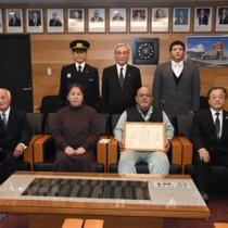 火災時の人命救助の功績による表彰を受けた佐平さん(前列右から2人目)と同席した洋子夫人(同3人目)ら=8日、奄美市役所