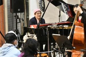 「島ぬクリスマス」でピアノを演奏する村松さん=13日、奄美市名瀬
