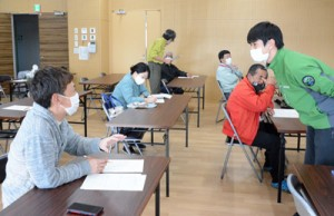 奄美群島国立公園について住民の意見を聞く環境省職員(右)=24日、和泊町役場