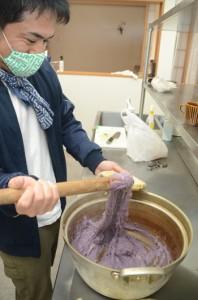 水煮したサツマイモと餅をすりこぎ棒で根気強く練りヒキャゲを作る荒波のやどりのスタッフ=18日、龍郷町幾里