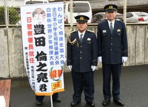 一日警察署長の委嘱を受けた豊田君(中央)=8日、徳之島町亀津