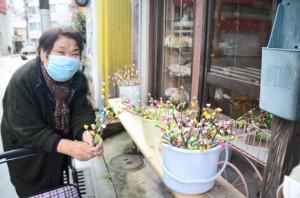 坂下さんの店で飾り付けられたナリムチの枝を買い求める女性客=11日、奄美市名瀬