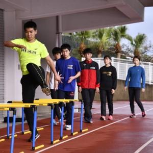 地元の中学生らと一緒にトレーニングに励む選手たち=11日、奄美市の名瀬運動公園陸上競技場