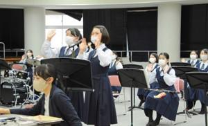 ウェブ交流会で画面の向こうに手を振る大島高校の生徒=22日、奄美市名瀬の大島高校