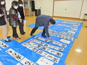 寄せられた作品を入念に確認する審査員=18日、龍郷町のりゅうがく館(提供写真)