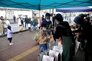 商店街の初商いで福袋を購入する買い物客=2日午前9時ごろ、同市名瀬
