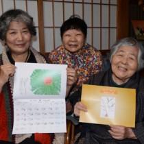 2021年カレンダー「奄美ゆらい暦」を発行した西代表(右)ら=6日、奄美市名瀬