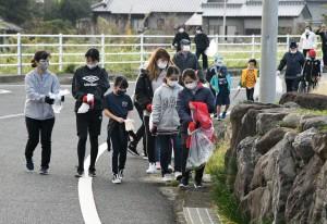 歩きながら道沿いのごみを回収する参加者=24日、天城町松原