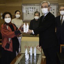 シルクの保湿成分を加えたアルコールハンドスプレーを寄贈したアーダンの西会長(左)ら=27日、奄美市役所
