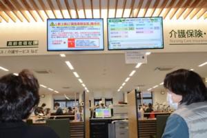 1都3県への緊急事態宣言を受けて来庁者に注意を喚起する奄美市役所内のモニター画面=8日、同市名瀬